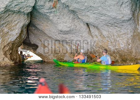 MELOS GREECE - SEPTEMBER 4 2012: People with kayaks exploring the caves at Filidas near Kleftiko at the southwest coastline of Melos island.