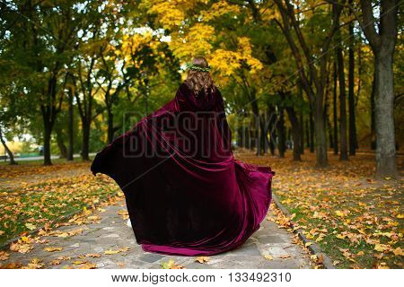 Beautiful girl with lantern in the scary autumn wood. Fantasy and Halloween image. Charming witch wearing mantle in the forest.