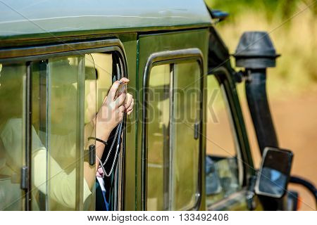 Kenya, Africa - March 7, 2016: Tourist taking pictures of animals out of safari tour truck in Kenya Africa