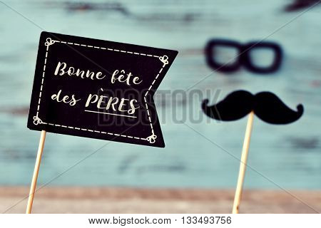 a black flag-shaped signboard with the text text bonne fete des peres, happy fathers day in french, and a mustache and a pair of eyeglasses forming the face of a man, against a blue rustic background