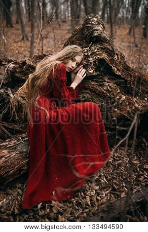 Young woman in red dress in the autumn forest