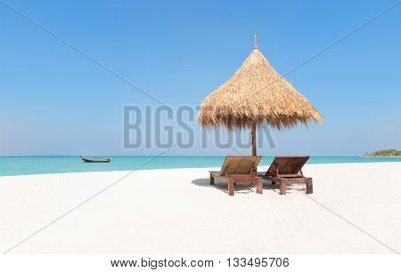 Wooden Deckchairs Under Straw Parasol On Tropical Beach With Boat.