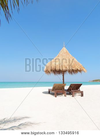 Wooden Deckchairs, Straw Parasol And Palm Trees On Paradise Beach.