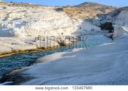 MELOS GREECE - SEPTEMBER 4 2012: Sarakiniko cove beach and gorge with people sunbathing and swimming.