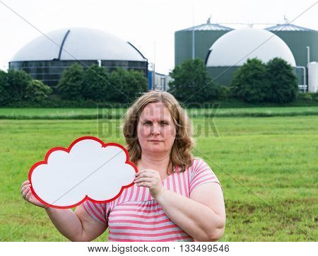 Woman holding a sign in front of a biogas plant