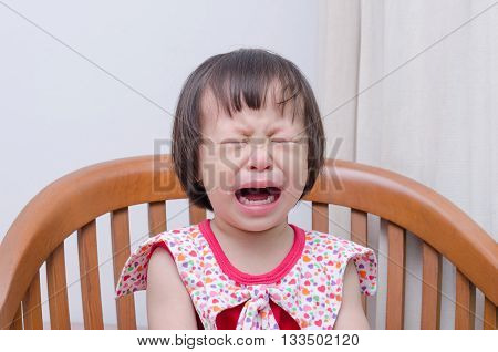 Portrait of  little Asian girl crying on chair