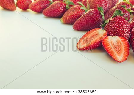 Cut strawberry on a white background. Sliced strawberry on strawberry background. Strawberry background. Macro. Texture. Frame with copy space. Fruit background. Spring summer background.