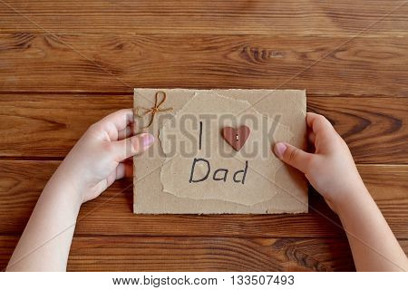 Child holds a birthday card for dad. Child holds a greeting card in hands. I love dad. Hand card out of cardboard, paper, wood buttons, cord. Simple quick gift idea. Kids creativity. Wooden background