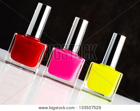 Three Bottles Of Nail Polish Standing On Sloping White Surface