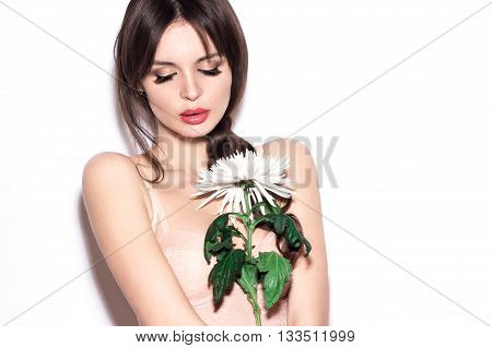 Beautiful sexy girl in lingerie-type bodice with delicate make-up and flower in hand. The beauty of the face. Photos shot in the studio on a white background.