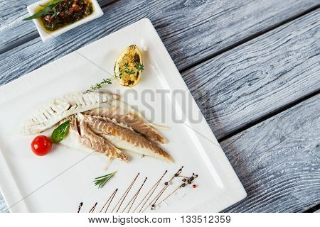 Fish fillet with lemon. Green herbs and cooked fish. Baked fillet of dorado fish. Healthy dish with herbal sauce.