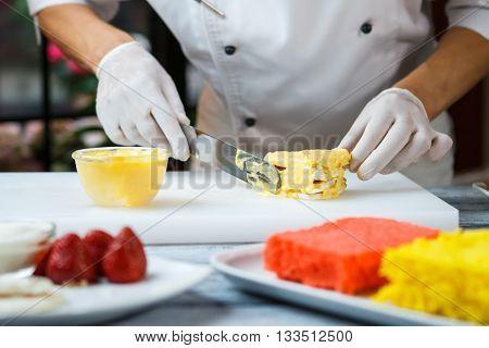 Hand with spatula touches shortcake. Shortcake smeared with custard. Chef prepares tasty dessert. Work in restaurant kitchen.