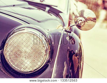 Shiny vintage car. Retro photo filter. Detail view of the headlight. Retro car. Front light. Retro automobile scene. Circle headlamp.