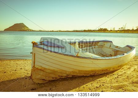 Old fashioned faded image style Old clinker design dinghy on beach