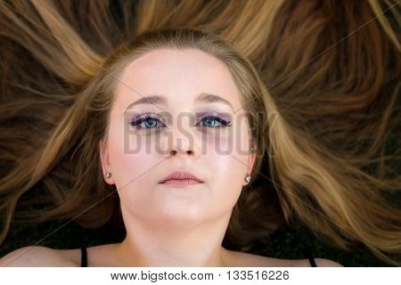 A beautiful teenage girl lays on the ground with her long blond hair spread out around her. She looks blankly up at the camera with just a hint of a smile in her eyes.