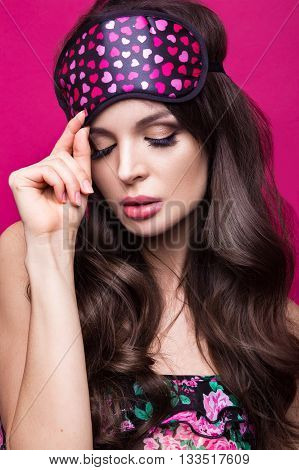 Funny young woman in sleeping mask and pajamas on a pink background. The beauty of the face. Photos shot in studio