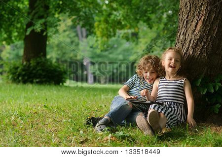The boy and the girl of 7-8 years sit under a tree having nestled and play on the tablet. Children are very keen. Them that - that has made laugh. Children laugh.