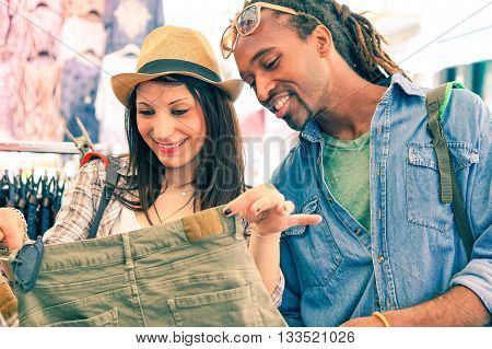 Interracial young couple searching clothing at street shop market - Multiracial happy friends positive facial expression and fun on shopping day - Concept of people sharing daily life - Focus on male