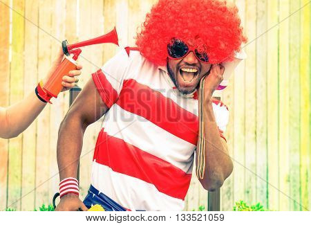 Afro american man fan of football have fun with bizarre look for international sport event - Black african male with funny wig is screaming deafened by unpleasant noise - Concept of health danger poster