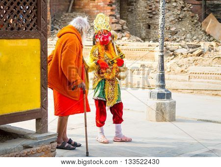 KathmanduNepal - March 2 2016: Sadhu Baba and Hanuman is talking near the collapsed Temple area of the Pashupatinath Temple.In Hindu culture people wear facial Mask to become Hanuman.Hanuman who is the incarnation of Lord Shiva.