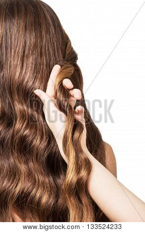 Hands hairdresser plait long wavy hair isolated on white background.