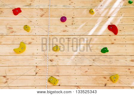 Colorful hand and footholds on a wooden indoor climbing wall in a close up full frame view for a recreational challenge or for practising for the extreme sport of rock climbing