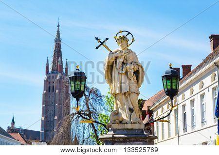 Bruges, Belgium - April 10, 2016: Statue of Johannes Nepomucenus, church tower Bruges, Belgium