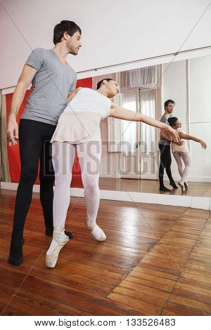 Full Length Of Trainer Practicing With Ballerina