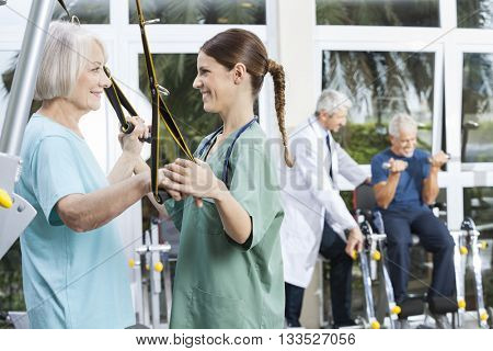 Smiling Nurse Assisting Senior Woman With Resistance Band Exerci