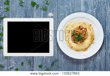 Hummus plate with copyspace at tablet screen. Hummus spread from chickpeas with veal stew.