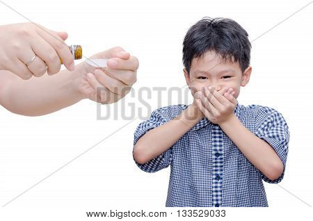 Asian boy close his mouth by hands ,don't want to take medicine from his mother