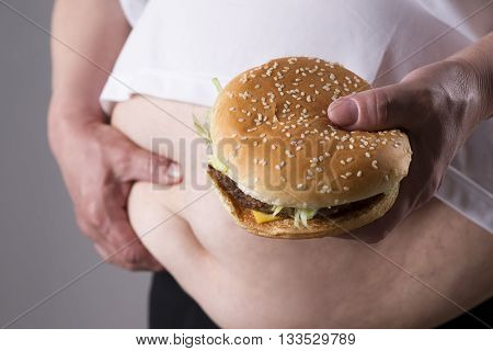 Women suffer from obesity with big hamburger in hand. Junk food concept on a gray background