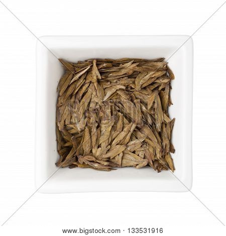 Longjing tea leaves in a square bowl isolated on white background