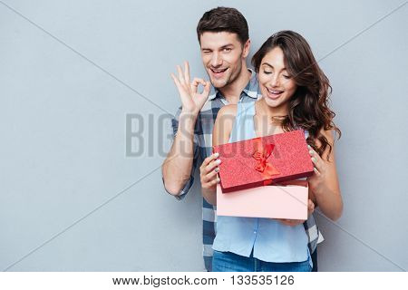 Young beautiful woman receiving a gift from her boyfriend showing ok sign isolated on gray background