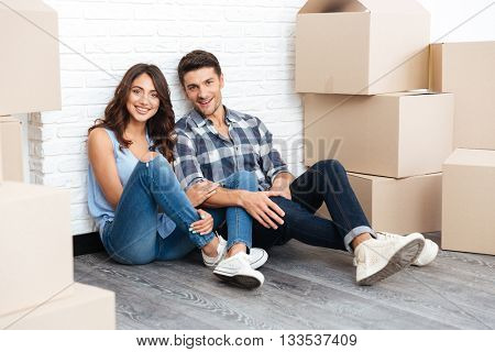 Young married couple sitting in their new house