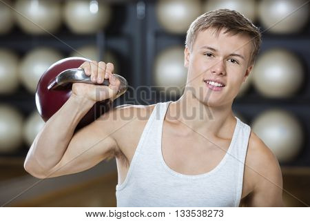 Attractive Young Man Exercising With Kettlebell In Gymnasium