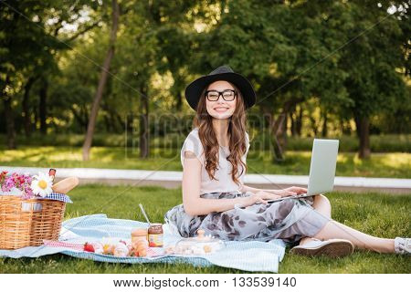 Smiling pretty young woman in hat and glasses using laptop on picnic in park