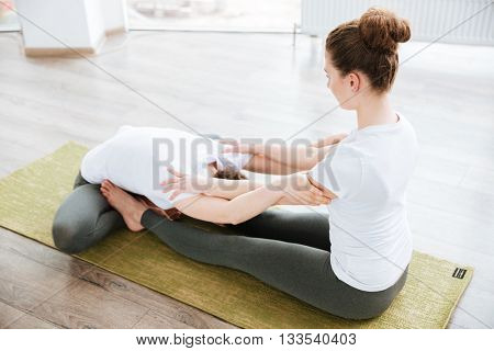 Two cute young women sitting and stretching in yoga center