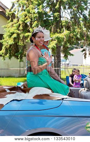 WEST ST. PAUL, MINNESOTA - MAY 21, 2016: Princess and Prince of West Wind for St. Paul Winter Carnival Alyssa Ortiz and Scott Oien wave to crowd at Grande Parade in West St. Paul on May 21.