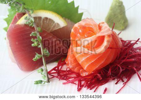 Japanese sashimi set consisting of salmon tuna hamachi radish slices and wasabe