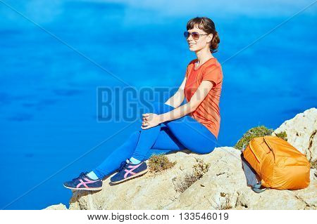 female traveler with backpack sitting on the cliff against sea and blue sky at early morning