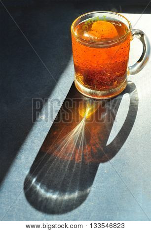 Glasses cup with black tea, top view. Pattern of refraction on table.