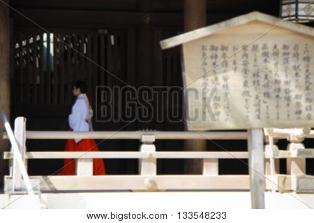 Blurred background with Japanese man in traditional clothing and hieroglyphs on a wooden plank, Meiji Shrine in Tokyo, Japan.