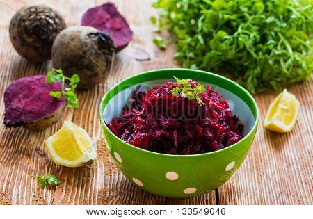 Salad: diet salad with beetroot, olive oil and lemon. Served in a bowl on wooden background. Beetroots, lemon and lettuce on kitchen table.