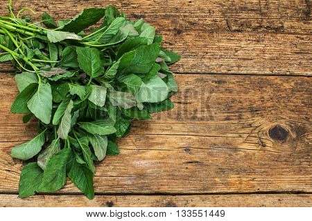 greens on a  brown wooden table background