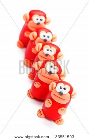 Row of clay toys (monkeys). Isolated on white background tilted