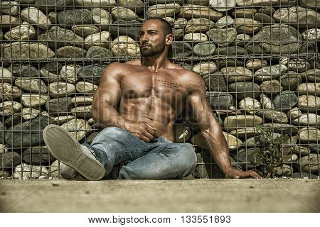 Handsome Muscular Shirtless Hunk Man Outdoor in City Setting, Sitting on the Ground. Showing Healthy Body While Looking Away to a Side