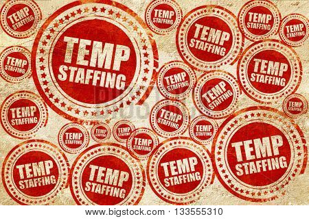 temp staffing, red stamp on a grunge paper texture
