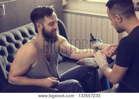 Male tattoo artist holding a tattoo gun showing a process of making tattoos on a male tattooed model's arm.