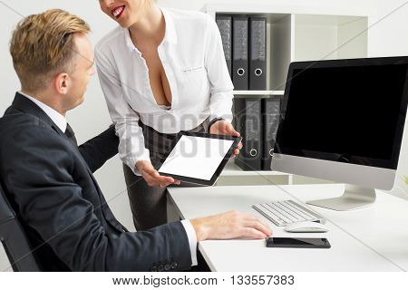 Secretary flirting and showing blank screen tablet to her boss